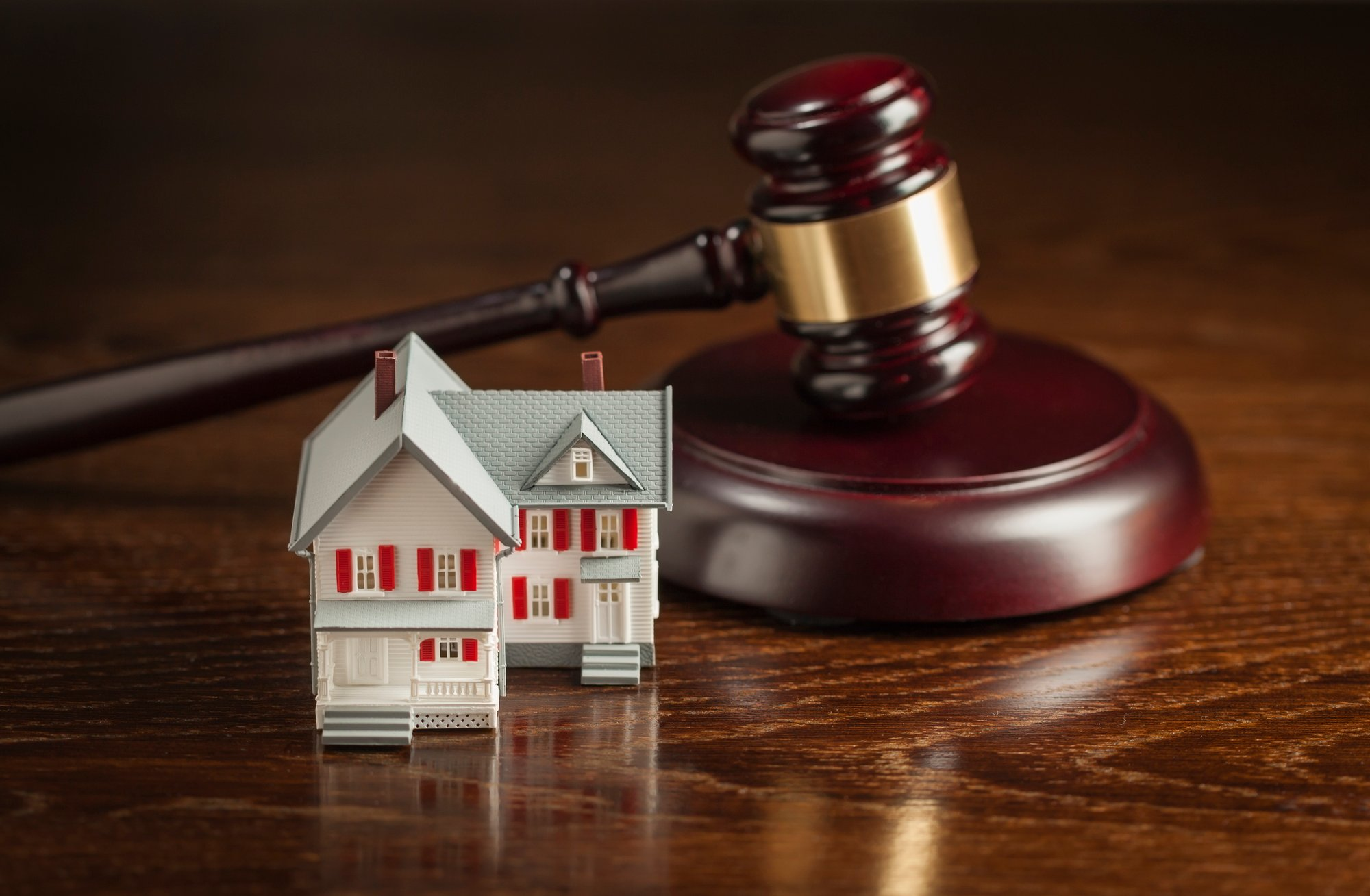 Gavel and Small Model House on Table