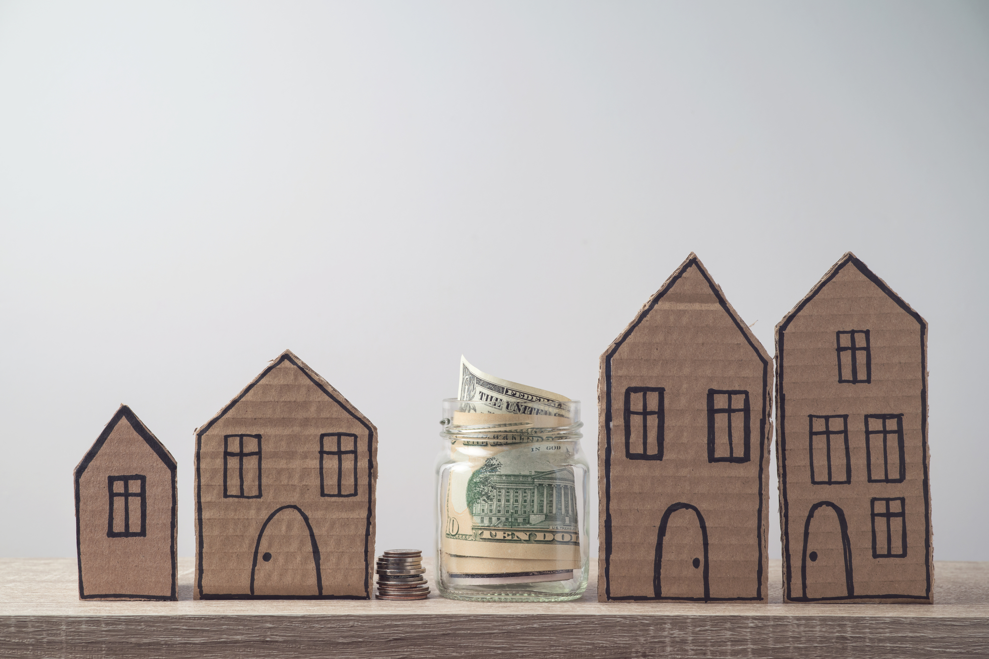 Property investment and house mortgage financial concept with money and cardboard houses