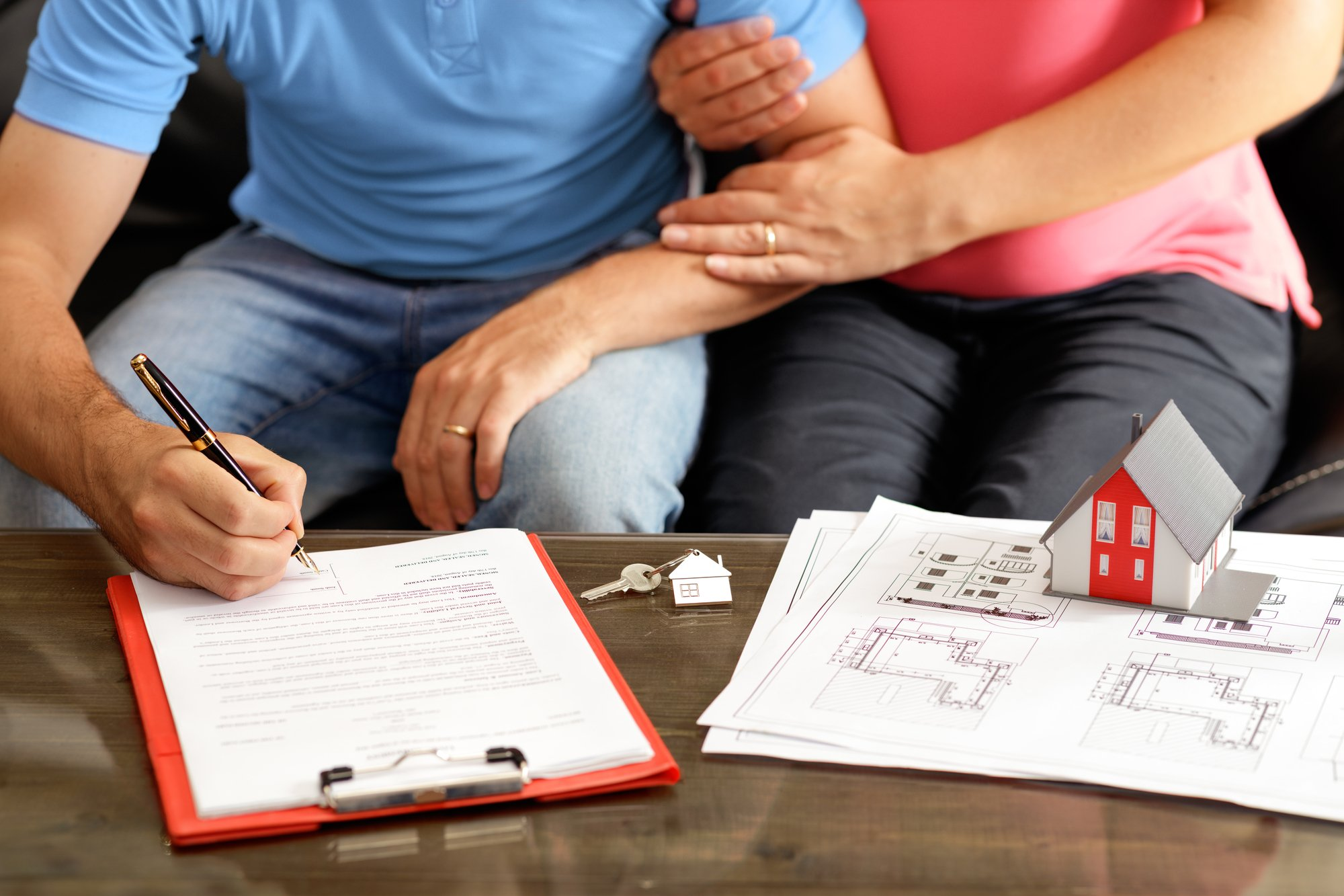 Young Couple Signing Loan Contract For House Purchasing