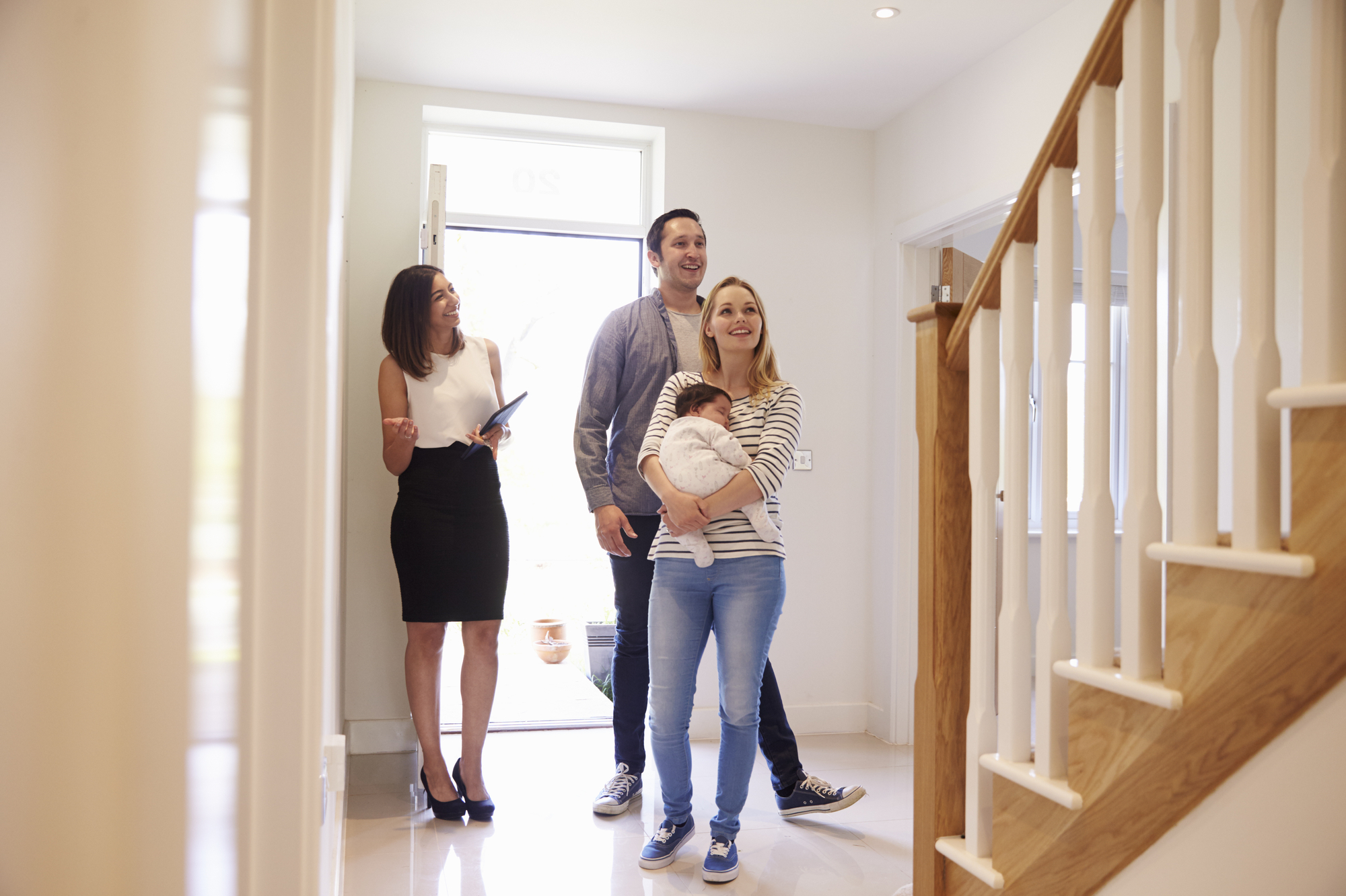 Realtor Showing Family Around Property For Sale