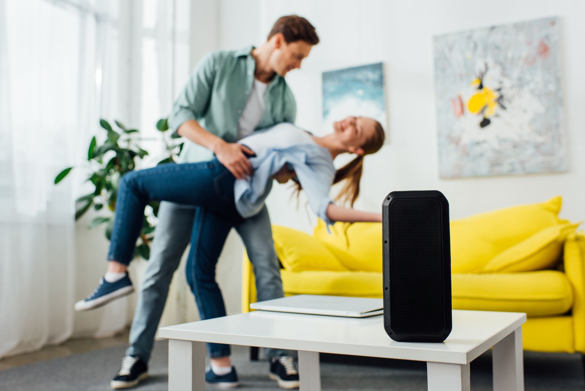 Selective focus of wireless speaker and laptop on coffee table and smiling young couple dancing at home
