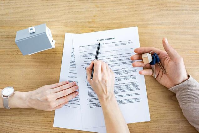 Top view of woman holding pen near document with rental agreement lettering and man with keys in hand (R) (S)